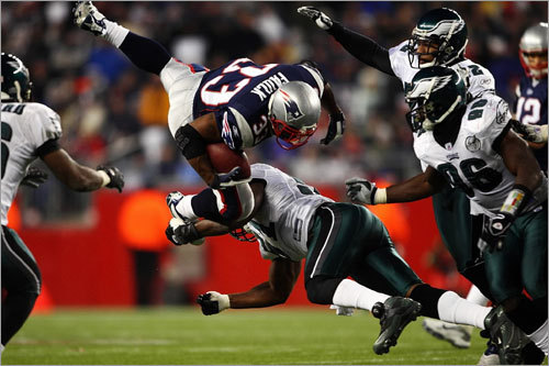 The Eagles' Takeo Spikes up-ended Kevin Faulk (top) of the Patriots.