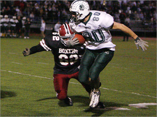 Dartmouth's Justin Mello (80) gets past Brockton's Brian Kelly.