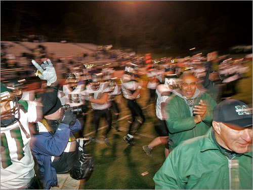 Marshfield players rush onto the field in celebration following a victory over Weymouth.