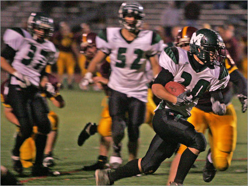 Marshfield running back Brad Poirier, right, rushes towards the end zone for a second-half score.