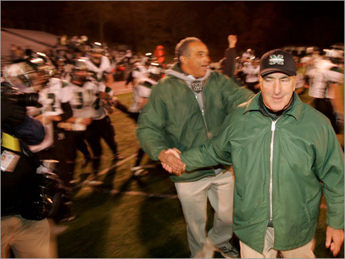 Marshfield football coach Lou Silva (center, with headset) is congratulated by an assistant after defeating Weymouth.