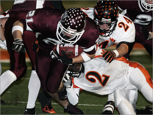Chelmsford running back Evan Sheridan (21) is brought down by Wayland's Michael Mitchell (2).