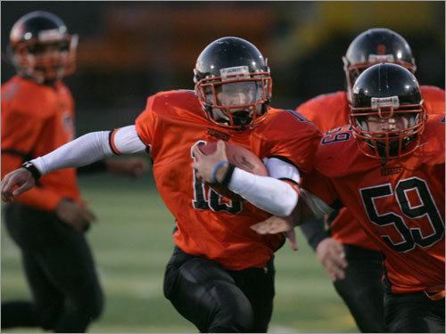 Greater Lawrence running back Nate Adames (10) carries the ball upfield with blocker Jorge Cruz (59) alongside.