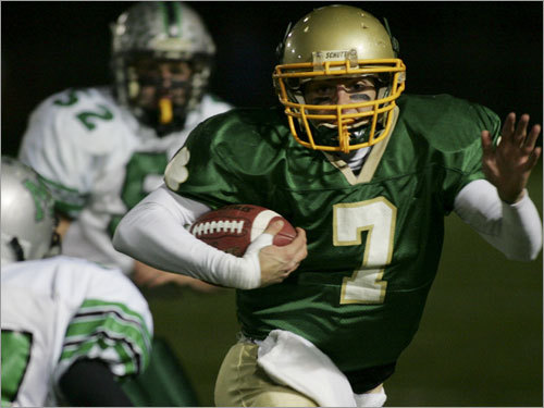 Bishop Feehan's Michael McGowan (7) looks to evade the tackle of Mansfield's Kairell Williams.