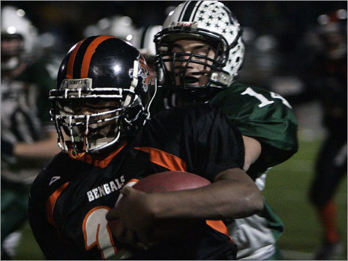Brighton running back Isaiah Long (20) tries to outrun Manchester Essex defensive back Pat Orlando (14).