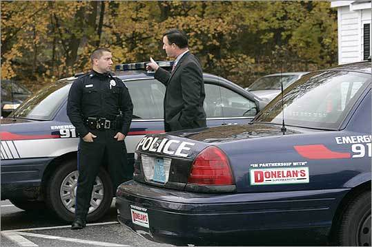 REVENUE SOURCE - Littleton adopted the 2005 proposal of Police Chief John Kelly (right, with Patrolman Pablo Fernandez) to sell advertising space, a plan that's generated $72,000 so far.