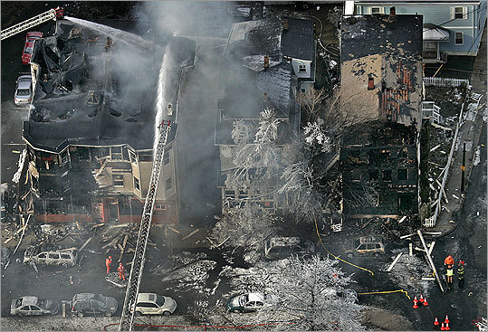 A building (center) on Main Street in Everett survived an inferno caused by the crash of a gasoline tanker yesterday, while its two neighbors were destroyed.