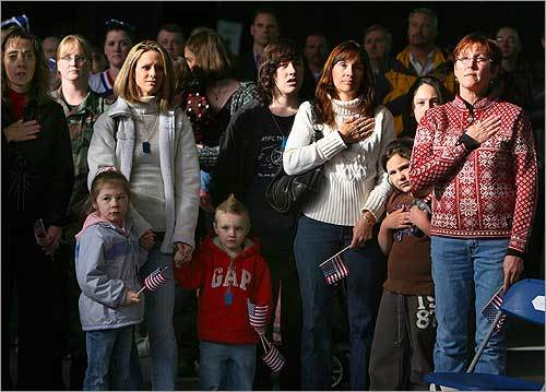 Several dozen troops who have returned from duty in Iraq in the past several weeks and months were honored at a welcome-home ceremony at Hanscom Air Force Base on Dec. 5. Family members paused to salute the flag during the national anthem.