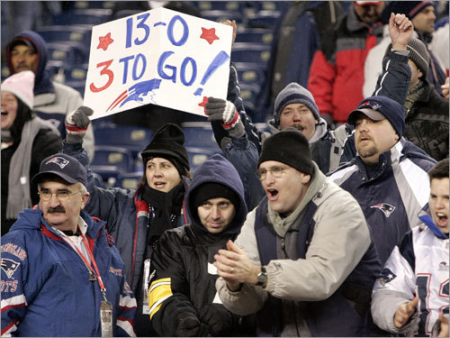 A fan displayed a sign reflecting the Patriots' latest win and how many more victories the team needs to finish off a perfect regular season.
