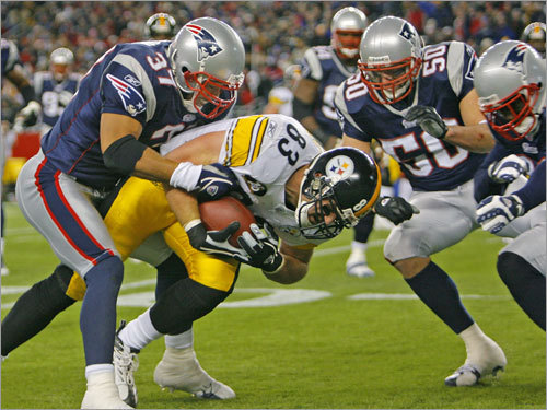 Steelers tight end Heath Miller found himself surrounded by Patriots as Rodney Harrison (37) brought him down.
