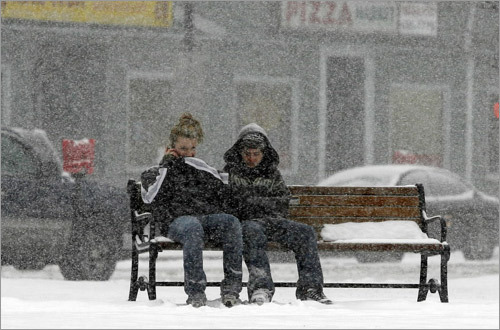 The storm coated Natick with snow. Allie Lucenta (left) and Anthony Bradle (right) made a phone call in the snow.