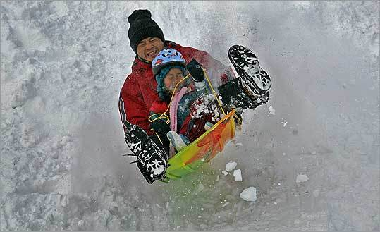 Bo He and his 5-year-old daughter, Ellen, tried to stay under control as they slid at Jamaica Pond yesterday.