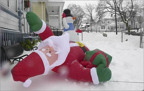 An inflatable Santa Claus display was blown to the ground during high winds and rain late Sunday morning as residents of the Wollaston neighborhood of Quincy were digging out of an overnight snowfall on Sunday.