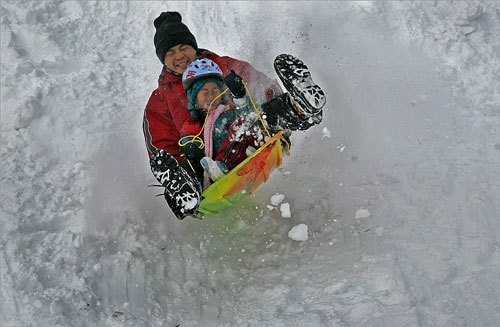 Bo He and his 5-year-old daughter Ellen enjoyed a bumpy sled ride down a hill at Jamaica Pond on Dec. 14. Three early snowstorms have pounded New England, contributing to near record-breaking snowfall accumulation for the month of December.