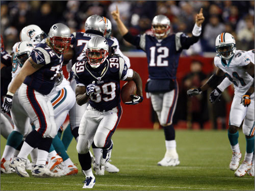 Laurence Maroney got some distance as Tom Brady celebrated in the background.