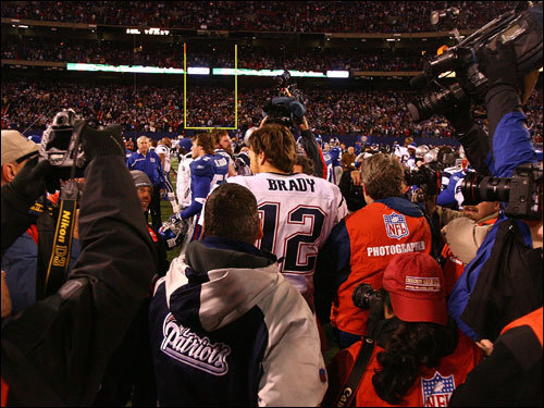 Tom Brady (center) was surrounded by media after beating the Giants and improving to 16-0 in the regular season.
