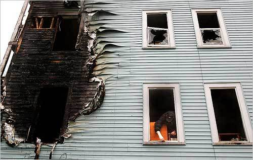 In Dorchester, a Boston Emergency Services employee cleared debris from a bedroom window in the Bellevue Street triple decker where a midnight fire killed two sleeping children. The two-alarm blaze started in the rear of the first floor.
