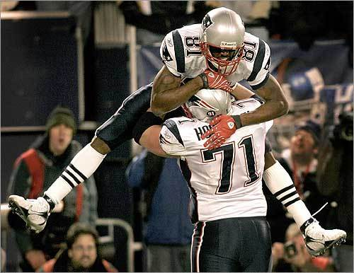 Patriots wide receiver Randy Moss celebrated with teammate Russ Hochstein after catching a 4-yard toss from Tom Brady in the second quarter of the Patriots-Giants game, setting a new NFL record for most points scored in a season. On the reception, Moss also tied the NFL record for touchdown receptions in a season, 22, set by Jerry Rice.