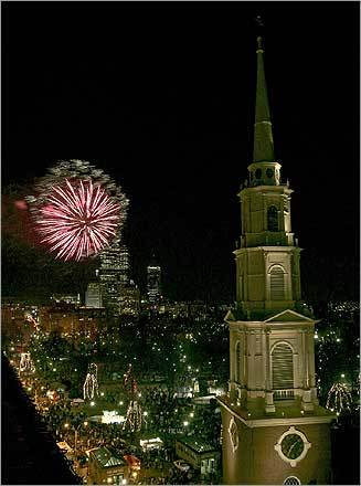 The view of the New Year's Eve fireworks display over Boston Common from the Suffolk Law School building. In the foreground is the Park Street Church, located at the corner of Park and Tremont streets.