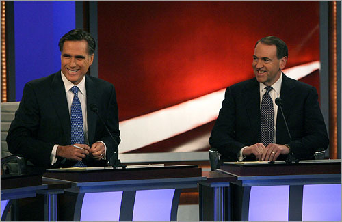Mitt Romney and Mike Huckabee (left to right) smiled during the debate. The grins soon disappeared though, as the two candidates scrapped over President Bush's foreign policy. Huckabee criticized Romney's past stances on the Iraq troop surge, while Romney accused Huckabee of launching personal attacks.