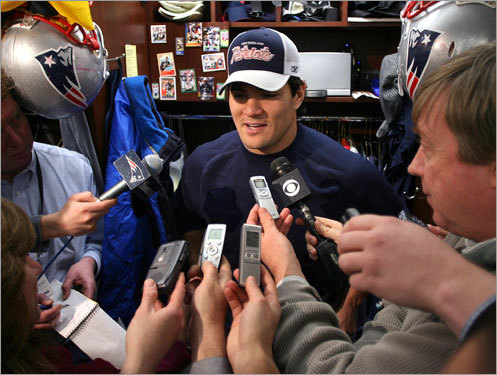 Tedy Bruschi grins and bears it as he is thronged by reporters at his locker.