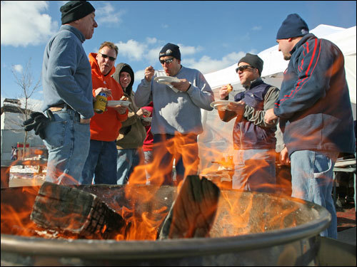 BIll Mahoney (center), of Billerica, kept warm and enjoyed a tailgating meal with his friends.