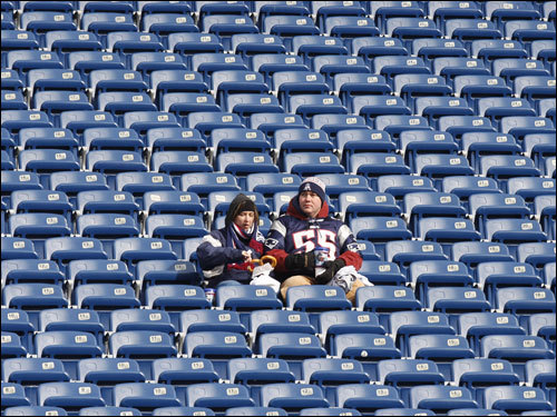 A pair of Patriots fans watched warm-ups while waiting for the start of the AFC Championship at Gillette Stadium.