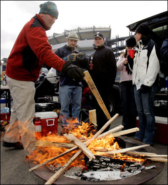 Fans stoked a fire while tailgating prior to the start of the game.