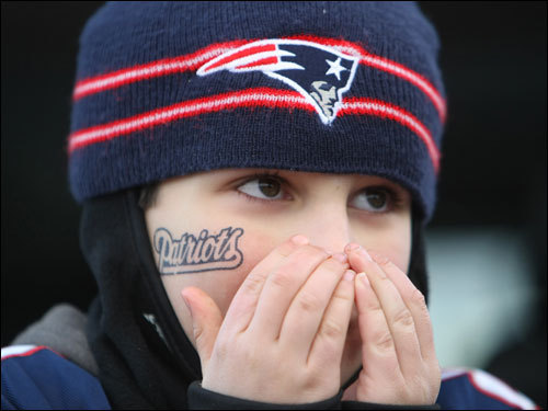 Sam Wisnia, age 10, of Weston, blew on his hands to keep them warm in the parking lot before the game.