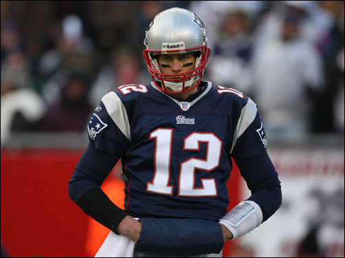Tom Brady tried to keep warm on the field during the game.
