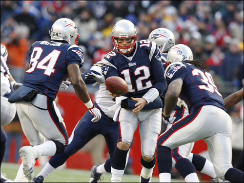 Tom Brady (12) handed off to Laurence Maroney (39) in the first half.