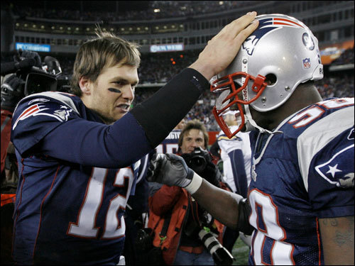 Tom Brady (left) and Pierre Woods (right) celebrated on the field.