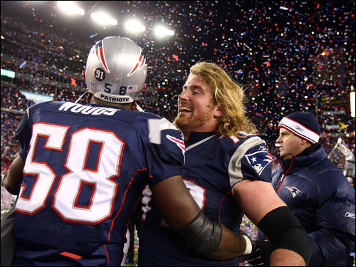 Patriots linebacker Pierre Woods (left) and Matt Light (right) embraced on the field during celebrations.