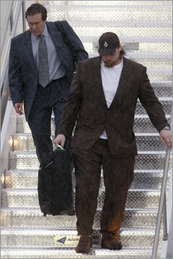 Coach Bill Belichick and offensive tackle Matt Light walk down the stairs to get off the team's flight to Arizona.