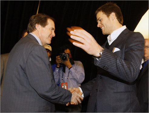 Coach Bill Belichick and league MVP Tom Brady shake hands at a news conference in Arizona.