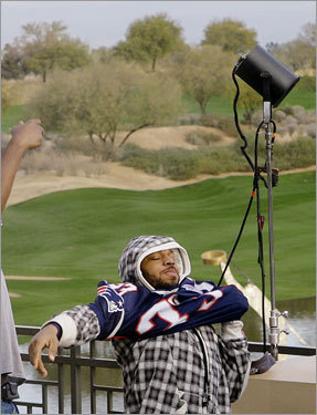Patriots running back Kevin Faulk (33) puts on his jersey as he prepares to enter a media availability at the team's hotel in Scottsdale, Ariz.