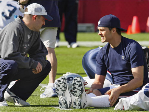 Patriots quarterback Tom Brady (right) talked with offensive coordinator Josh McDaniels during the team's practice on Wednesday.