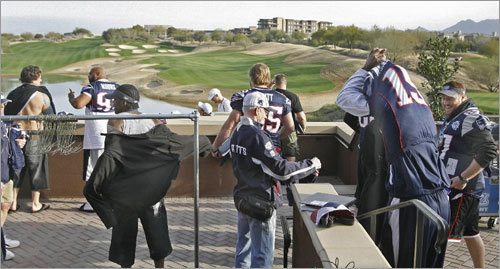 Players put on their team jerseys outside on a deck overlooking the golf course and close by mountains.