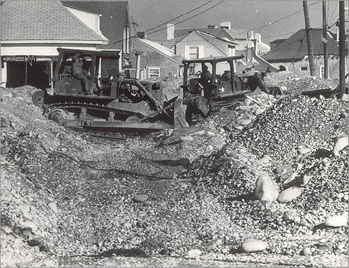 National Guard bulldozers had to be brought to Town Way in Scituate to clear the huge piles of rocks and sand pushed from the shore inland.