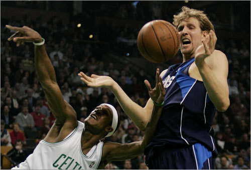 Boston's Rajon Rondo and Dallas' Dirk Nowitzki both reach for the ball during first half action at the TD Banknorth Garden Thursday evening.