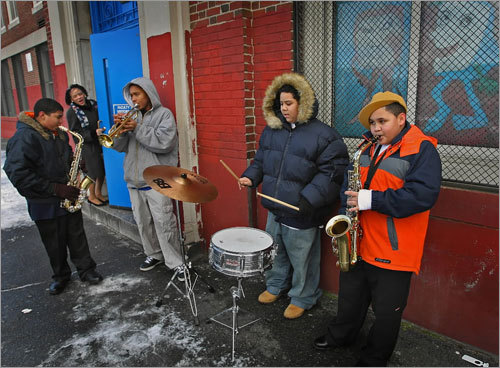 Left to right, Pedro Pouriet, Terrance Booth, Antonio Diaz, and John Inoa played musical instruments outside doorway of the Edwards Middle School in Charlestown as Dr. Carol Johnson, superintendent of Boston Public Schools, arrived. The Boston Pops helped bring $25,000 musical instruments to the school.