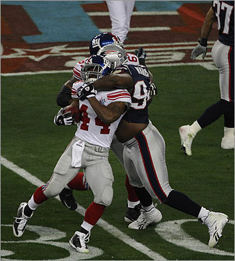 Ty Warren (94) tackled Ahmad Bradshaw (44) in the first quarter.