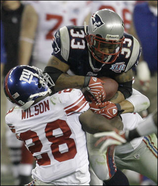 Patriots running back Kevin Faulk was tackled by Giants safety Gibril Wilson (28) in the third quarter.
