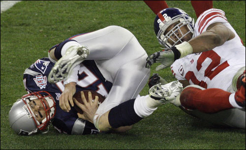 Tom Brady (left) was brought down by Giants Michael Strahan (right) in the third quarter.