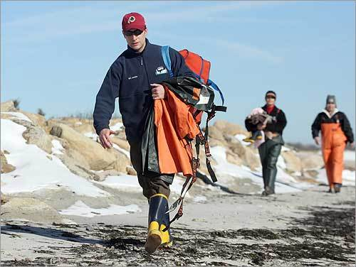 Cape Cod Stranding Network workers, including (from left) assistant stranding coordinator C.T. Harry, necropsy coordinator Katie Pugliares, and Americorps volunteer Iman Olguin-Lira, carried equipment to where the seal was located.