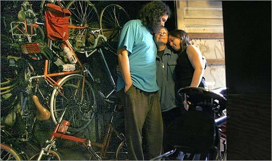 Harriet Fell was hugged by her two children, George and Tova, in Newton on Tuesday amid part of her husband's collection of bicycles.