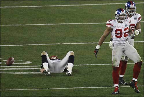 Patriots Tom Brady got sacked in the third quarter and New York Giants' Michael Strahan (92) and Osi Umenyiora (72) celebrated the sack. New England Patriots played against the New York Giants in Super Bowl XLII on Sunday, Feb. 3 in the University of Phoenix Stadium.