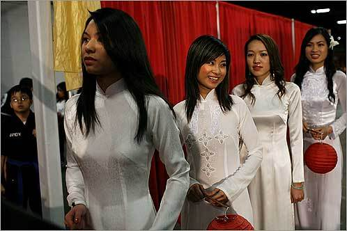 Members of the New England Intercollegiate Vietnamese Student Association (from left) Anne Tran, Chau Truong, Xuan Vong, and Lan Tran waited before going on stage to model Vietnamese dresses during The Tet in Boston Festival at the Bayside Expo Center in Dorchester on Saturday, Feb. 2. Tet is the Vietnamese Lunar New Year and is held to welcome the return of spring and to celebrate the Year of the Rat.