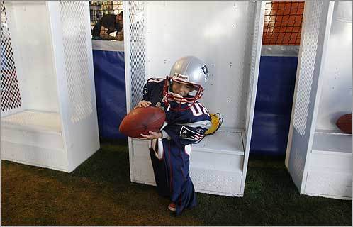 Patrick Quigley, 4, of Redondo Beach, Calif., tried on a New England Patriots' uniform at the NFL Experience. It was built by the Home Depot in the West Parking Lot adjacent to the University of Phoenix Stadium. The proceeds from the tickets sales will be donated by the NFL to the NFL/Youth Education Town.