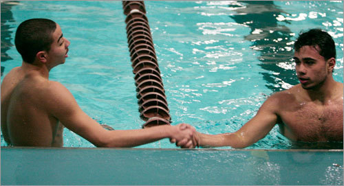 Corrado Addonisio of O'Bryant, left, shakes hands with Juan Velez of East Boston following the 100 freestyle during the Boston City championships at the Madison Park Community Center.